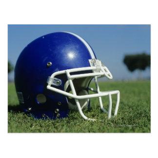 American football helmet in grass,close-up postcard