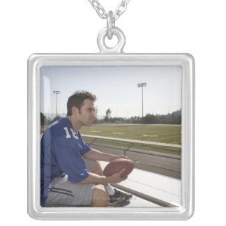 American football player sitting on bleachers silver plated necklace