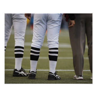American football players and coach standing on print