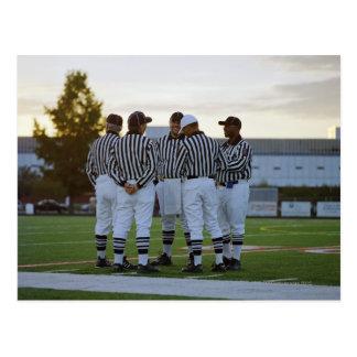 American football referees talking in field postcard