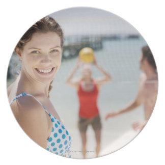 Amigos que juegan a voleibol en la playa plato