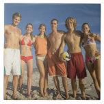 Amigos que presentan en la playa con voleiboles azulejos