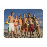 Amigos que presentan en la playa con voleiboles imanes de vinilo