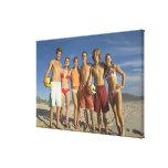 Amigos que presentan en la playa con voleiboles impresion de lienzo