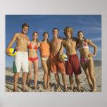 Amigos que presentan en la playa con voleiboles impresiones