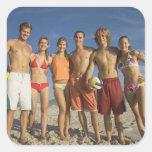 Amigos que presentan en la playa con voleiboles calcomanías cuadradass