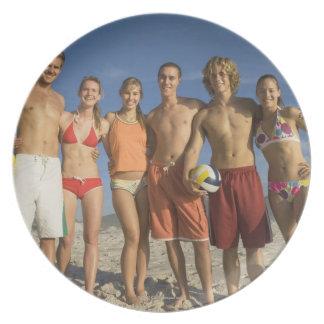 Amigos que presentan en la playa con voleiboles platos