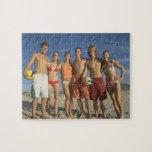 Amigos que presentan en la playa con voleiboles puzzles