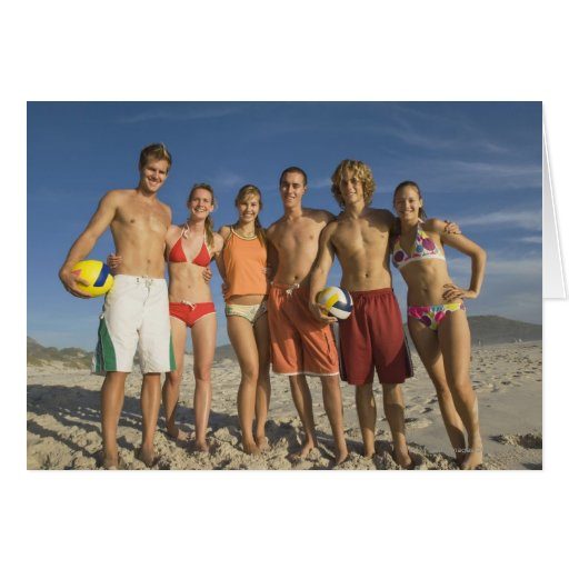 Amigos que presentan en la playa con voleiboles tarjetas