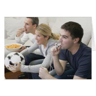 Amigos que ven la TV con el silbido, fútbol y Felicitacion