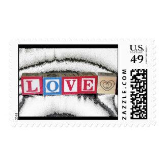 Amor deletreado hacia fuera en los bloques del timbres postales