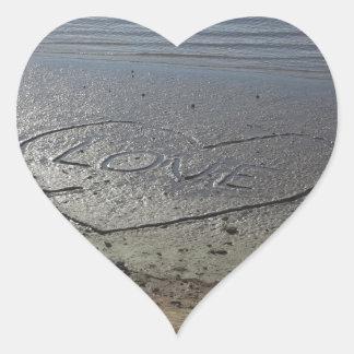 Amor escrito en la arena pegatina en forma de corazón