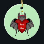 """Amorous funny Gothic Christmas bat Ceramic Ornament<br><div class=""""desc"""">Cute vampire bat holding a big red heart and wearing a yellow star headband cartoon art on a round ornament. The wording reads """"Xmas is love"""".</div>"""