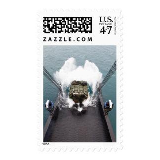 Amphibious assault vehicles disembark from USNS Postage
