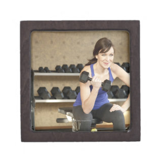 An active female lifting weights in a private gift box