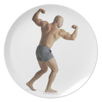 an adult caucasian male bodybuilder shows off party plates