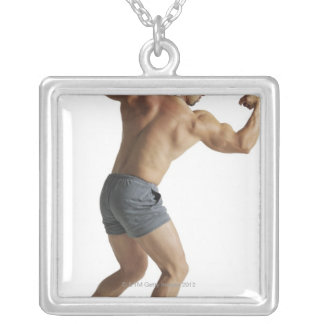 an adult caucasian male bodybuilder shows off silver plated necklace