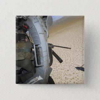 An aerial gunner scans terrain button