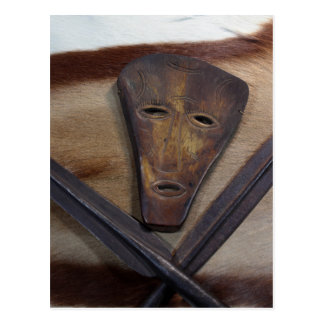 An African mask with a spear on an antelope skin. Postcard
