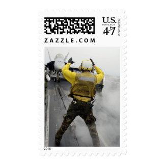 An aircraft director signals a F/A-18C Hornet Stamp