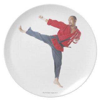 an asian male karate black belt wearing a red melamine plate