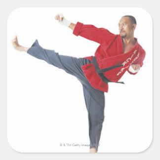 an asian male karate black belt wearing a red square sticker