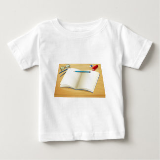 An empty notebook above the wooden table tee shirt