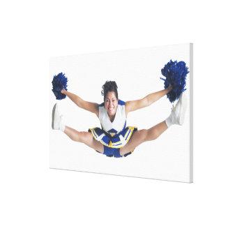 an ethnic teenage female cheerleader jumps high canvas print