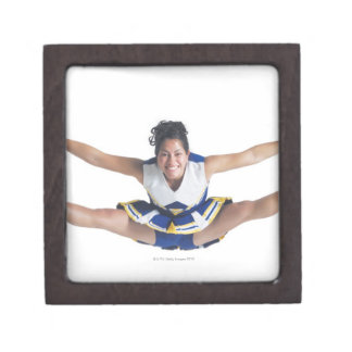 an ethnic teenage female cheerleader jumps high gift box