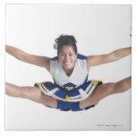 an ethnic teenage female cheerleader jumps high large square tile