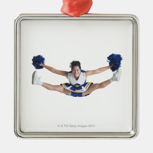 an ethnic teenage female cheerleader jumps high metal ornament