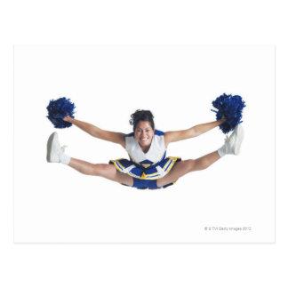 an ethnic teenage female cheerleader jumps high postcard