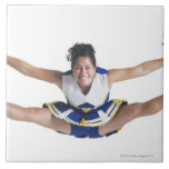 an ethnic teenage female cheerleader jumps high tiles