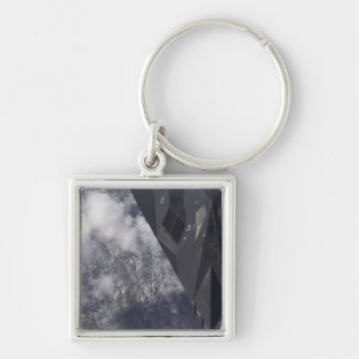 An F-117A Nighthawk flies high over the mountai Silver-Colored Square Keychain