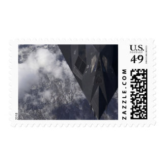 An F-117A Nighthawk flies high over the mountai Postage Stamps