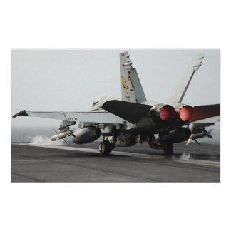 An F/A-18C Hornet launches from the flight deck Poster