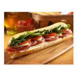 An Italian sub sandwich with 2 Post Cards