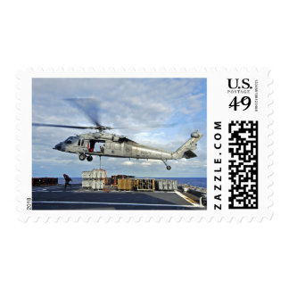 An MH-60S Seahawk prepares to deliver ammunitio Stamp