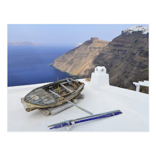 An old boat on the roof of a house in Santorini Postcard