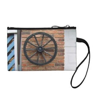 An old cart wheel on a brick wall change purse
