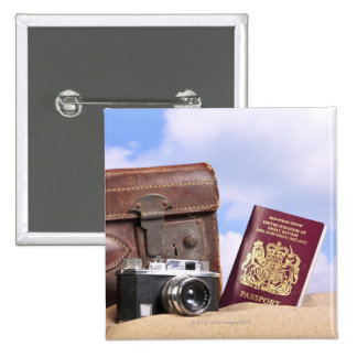 An old leather suitcase, retro camera and 2 inch square button