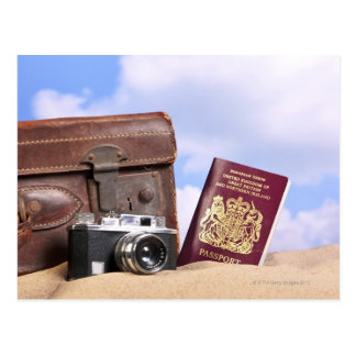 An old leather suitcase, retro camera and postcard