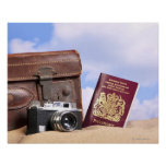 An old leather suitcase, retro camera and poster