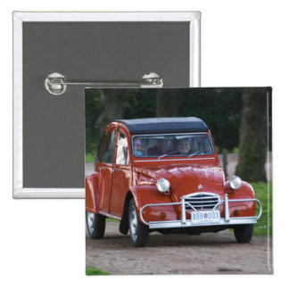 An old red Citroen 2CV car with a smiling woman Button