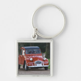 An old red Citroen 2CV car with a smiling woman Keychain