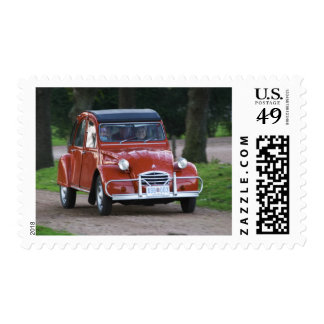 An old red Citroen 2CV car with a smiling woman Postage