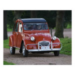 An old red Citroen 2CV car with a smiling woman Poster