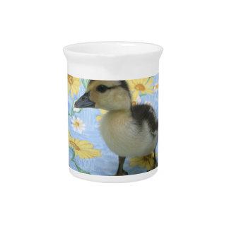 anadón del bebé en el fondo florecido dejado jarra para bebida