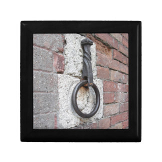 Ancient iron hoop hanging on stone wall gift box