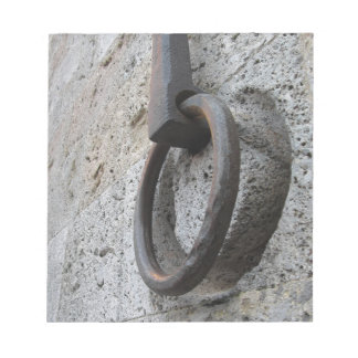 Ancient iron hoop hanging on stone wall notepad